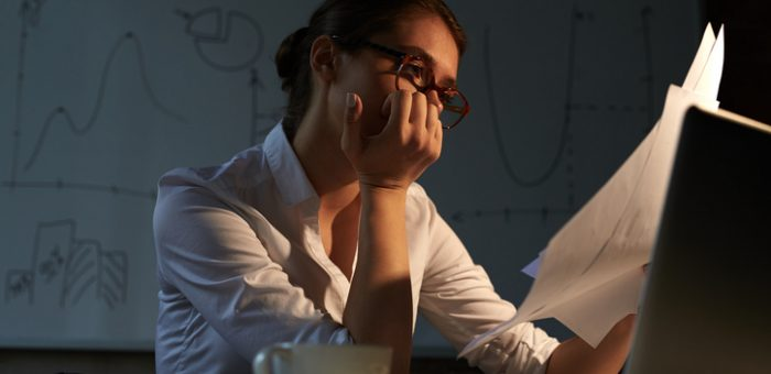 Tired accountant looking through papers in office at night